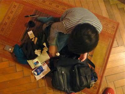 Vogelperspektive: Kind sitzt auf dem Boden und räumt schwarzen Lederrucksack aus