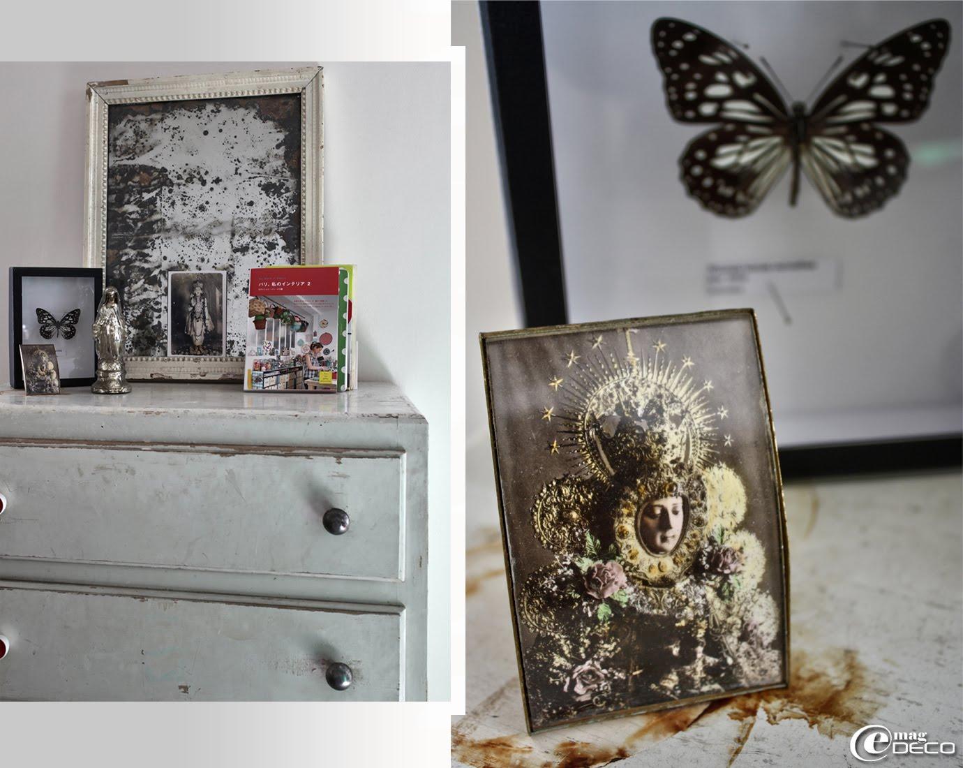 Posé sur une commode rapportée de chez Emmaüs, un vieux miroir et des bondieuseries chinées