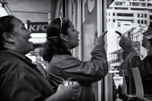 Two women point through the window of the KFC on Long street Cape Town.