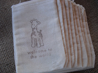 Stack of ten lightweight muslin natural-color bags with a baby giraffe image and the words, welcome to the world, stamped on the front in a dark tan or light brown.