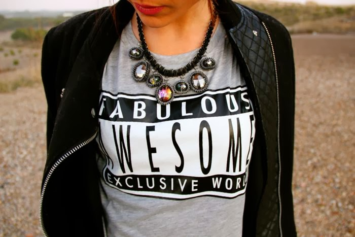 collar piedras, camiseta mensaje, abrigo negro cremalleras