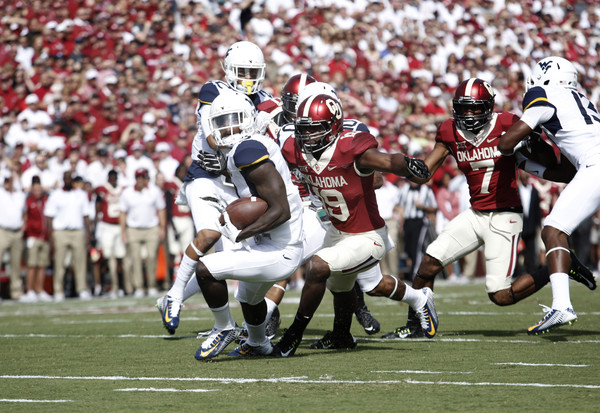 Linebacker Eric Striker #19 of the Oklahoma Sooners hits kick returner KJ Dillon #9 of the West Virginia Mountaineers October 3, 2015 at Gaylord Family-Oklahoma Memorial Stadium in Norman, Oklahoma. Oklahoma defeated West Virginia 44-24.