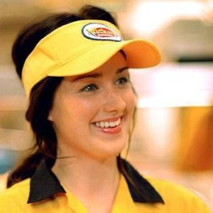 a pretty girl with a hat working in a fast food restaurant smiles