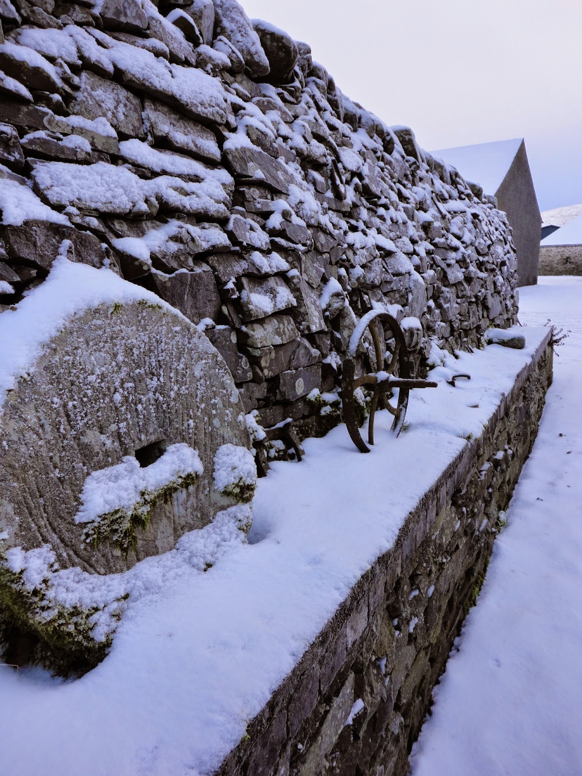 country farm wall with curling stones and snow in winter in scotland