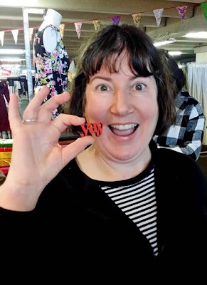 Woman holding up a brooch in the shape of the word 'yay' next to her mouth.