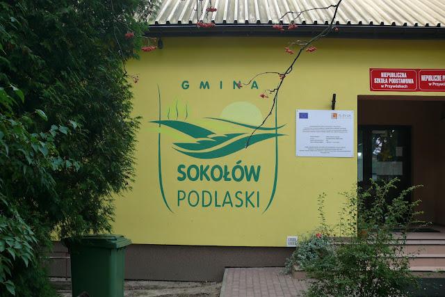 Ręczne malowanie loga na ścianie, logo gminy sokołów, logo ręcznie malowane na elewacji