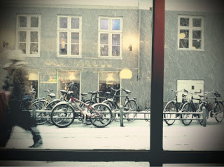 warm cafe Copenhagen looking out at winter snow bikes bicycle