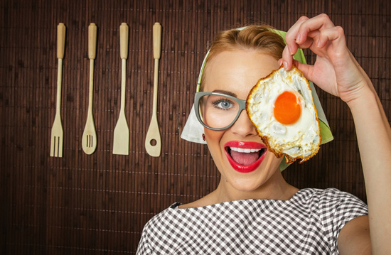 woman smiling with holding a fried egg