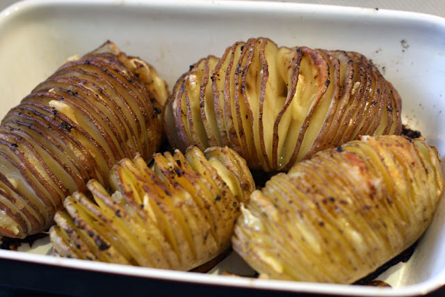 Close-up of 4 hasselback potatoes baked.