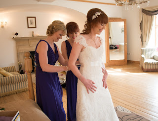 Bridesmaids helping dress the bride in her lace wedding gown with a jewelled headband accessory.