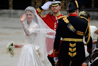Kate Middleton wave to the crowd on her wedding day as she enters Westminster Abbey. Her veil is made of layers of soft, ivory silk tulle with a trim of hand-embroidered flowers, also embroidered by the Royal School of Needlework.