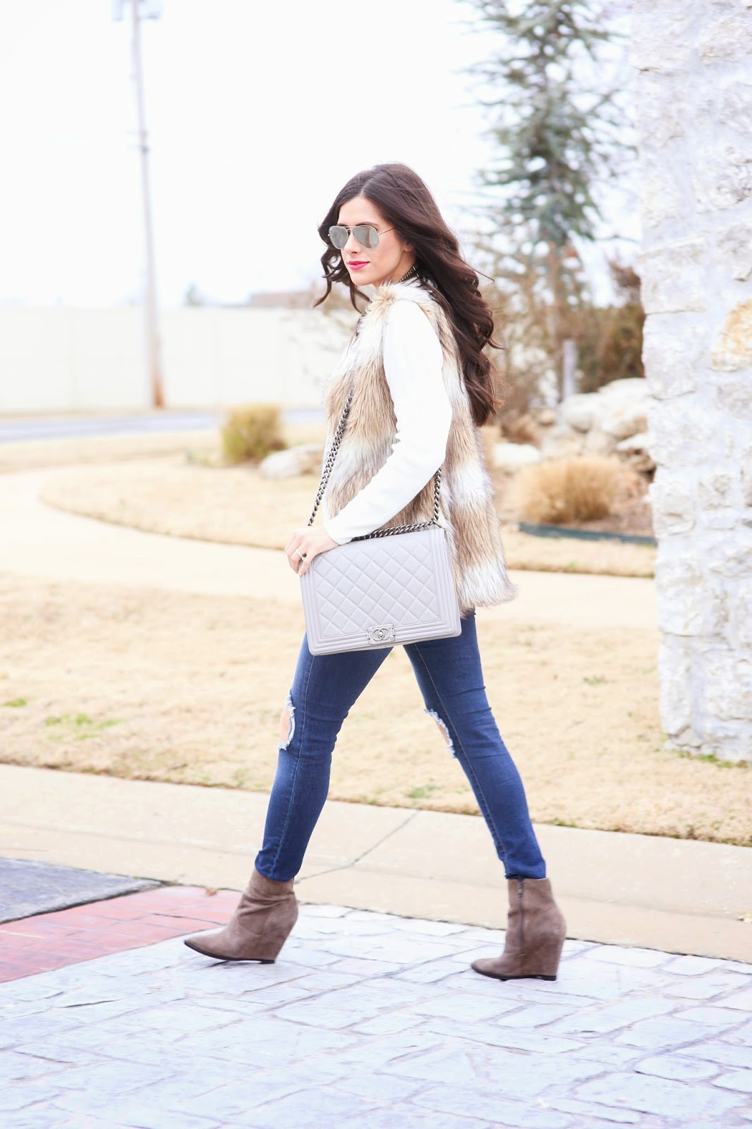 faux fur vest, chic wish fur vest, ripped jeans, knee ripped jeans, grey chanel boy bag, the courtey bibb, bauble bar courtney bib with pearls, emily gemma, cream v neck sweater, michael hors runway watch in gold, ash jasmine booties, taupe booties, wedged booties in taupe
