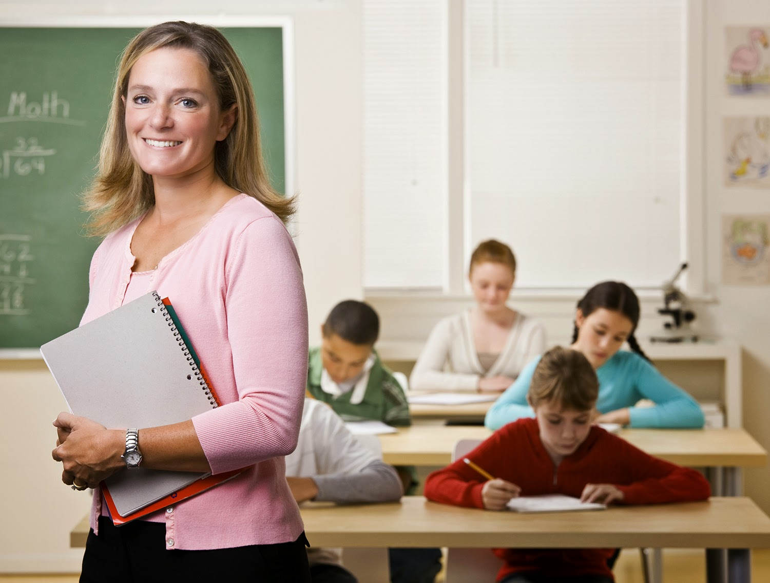 image of a school teacher smiling at camera.  Students working in background.