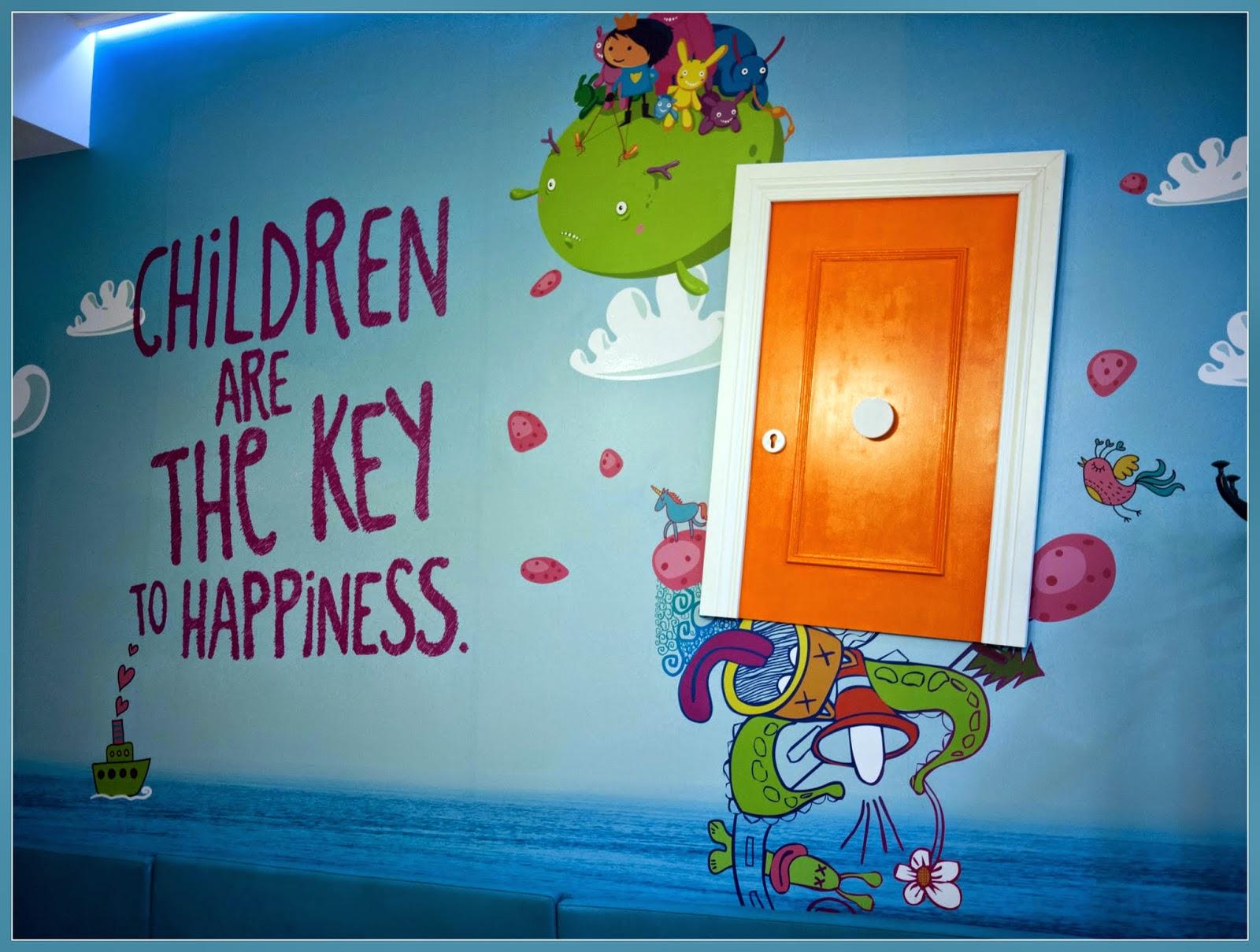 """Pared pintada con el mensaje """"Los niños son la llave de la felicidad"""""""