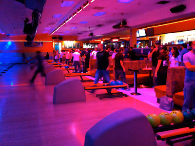 Bowling alley with colorful lights and people bowling