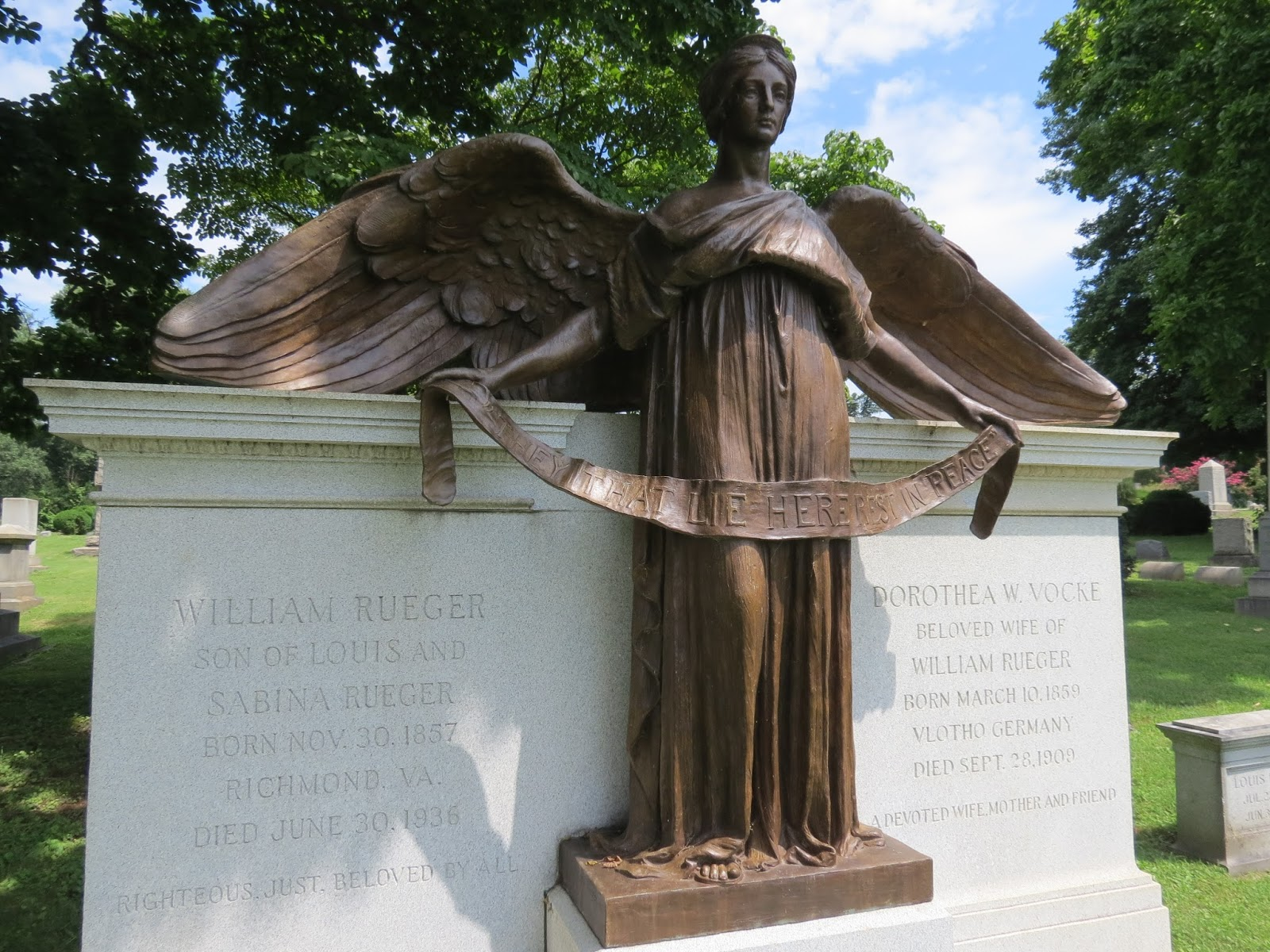 The Bronze Angel Above Is Holding A Banner That Says