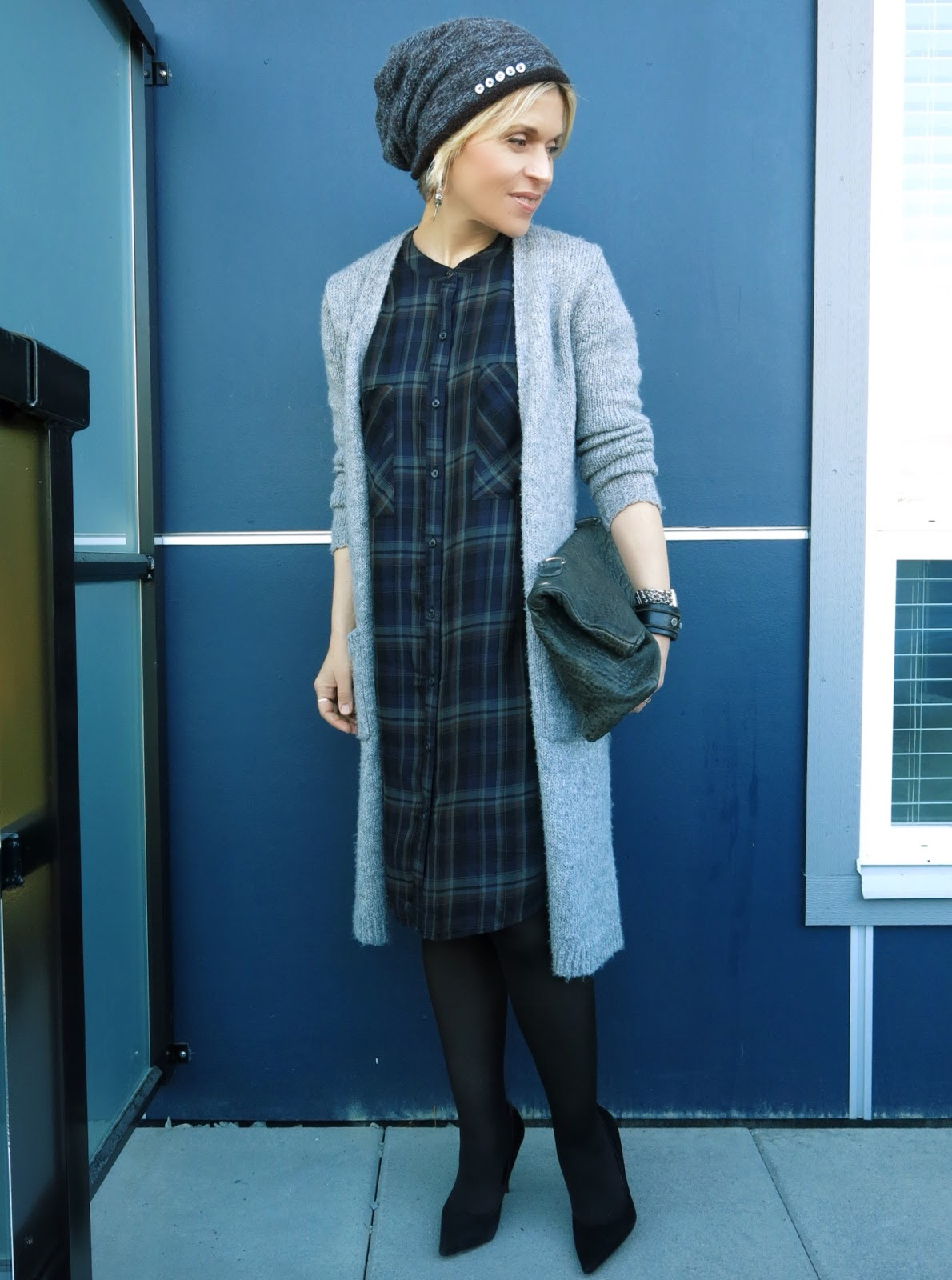 styling a plaid shirtdress with a long cardigan, black tights and pumps, and a woolen beanie