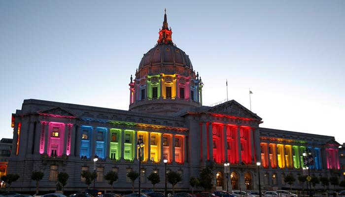 A Casa Branca, pela entrada da noitinha, com iluminação especial em diversas cores, celebrando a decisão histórica da Suprema Corte americana.