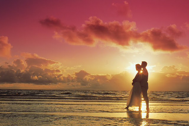 Couple embraces romantically on the beach during a beautiful sunset.