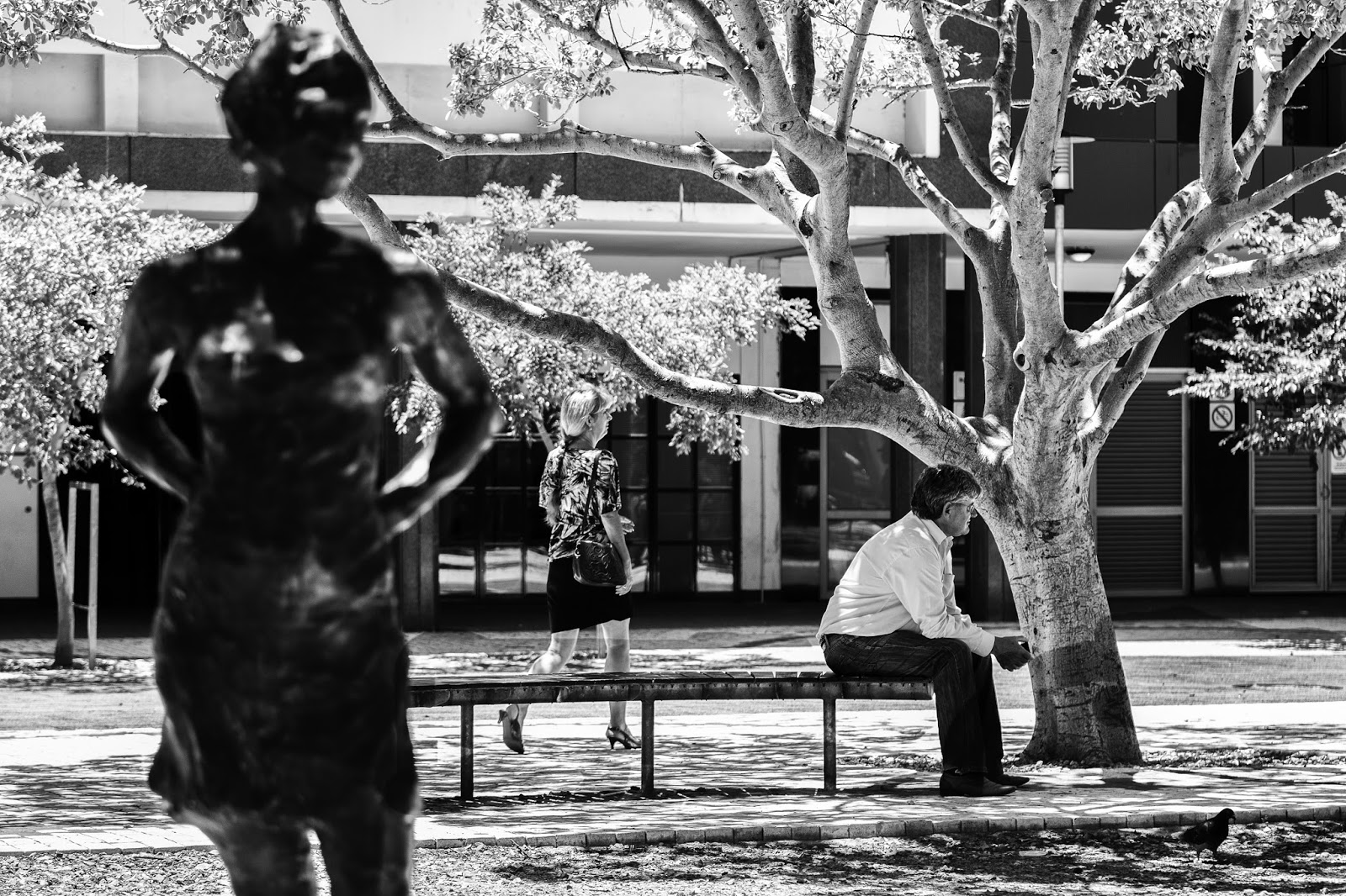 A man sits on a bench behind a statue of a woman while another woman walks past