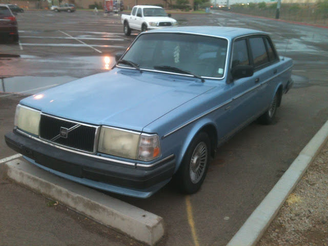 Blue 1986-1992 Volvo 240 GL sitting in parking lot after rainstorm