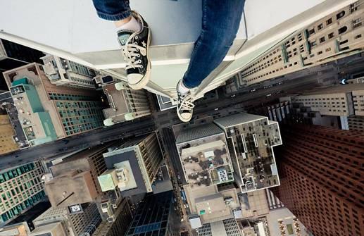 memotred dari atap - tren baru - Sebuah pemandangan yang diambil dari puncak gedung pencakar langit. Gaya memotret dari langit-langit mengharuskan fotografer menggantung di gedung pencakar langit untuk menangkap gambar yang sempurna