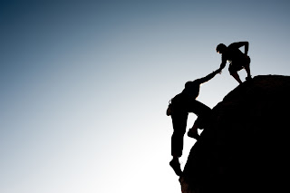 Men on top of rock helping other man up.