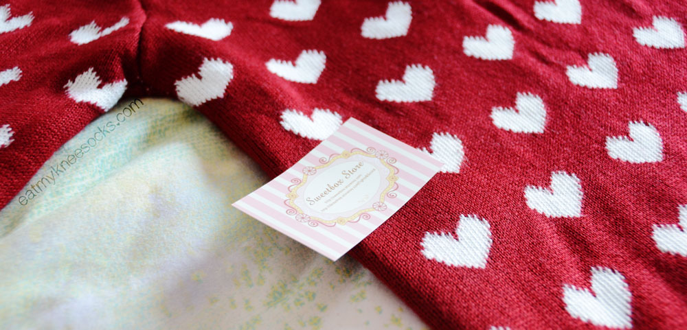 The wine red heart sweater and pink business card from Sweetbox Store.
