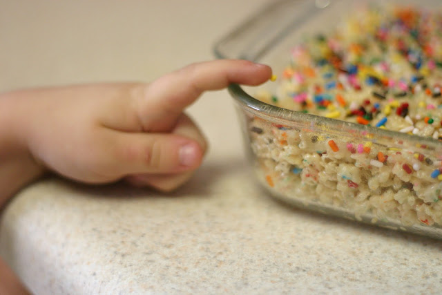 Hand of child sneaking colorful sprinkles