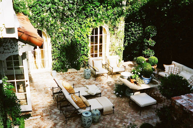 brick lined outdoor patio with metal lawn chairs with neutral cushions, a matching sofa and ottoman, lots of potted plants and Chinese porcelain garden stools. The exterior walls of the house are covered in ivy