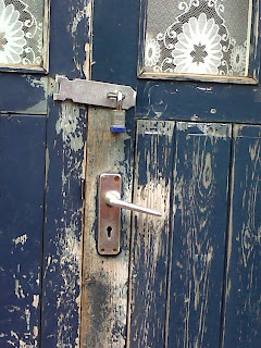 Photo of a battered door witth peeling blue paint