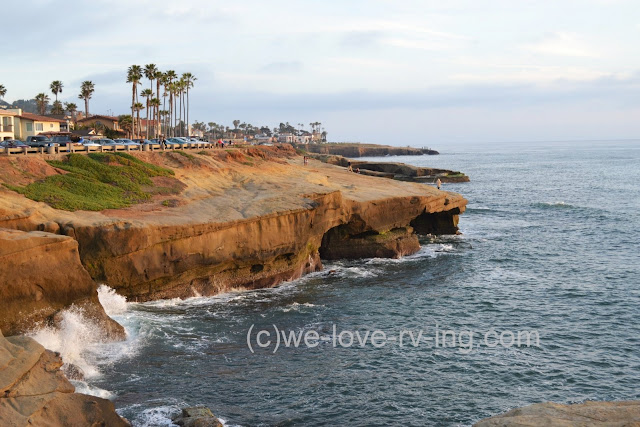 The setting sun casts a warm glow on the cliffs of Point Loma