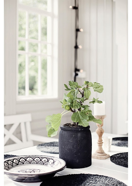 Dark grey planter with Moroccan inspired plates on a grey front porch dining room