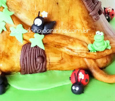 Bolo decorado Smurfs no formato de uma casinha tronco de árvore com porta, cogumelos, joaninha, formiguinha e sapinho decorando a casinha tronco de árvore.