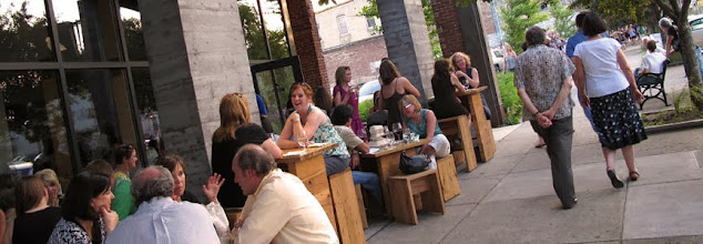 people sitting at tables in nulu area of louisville with a building on the left