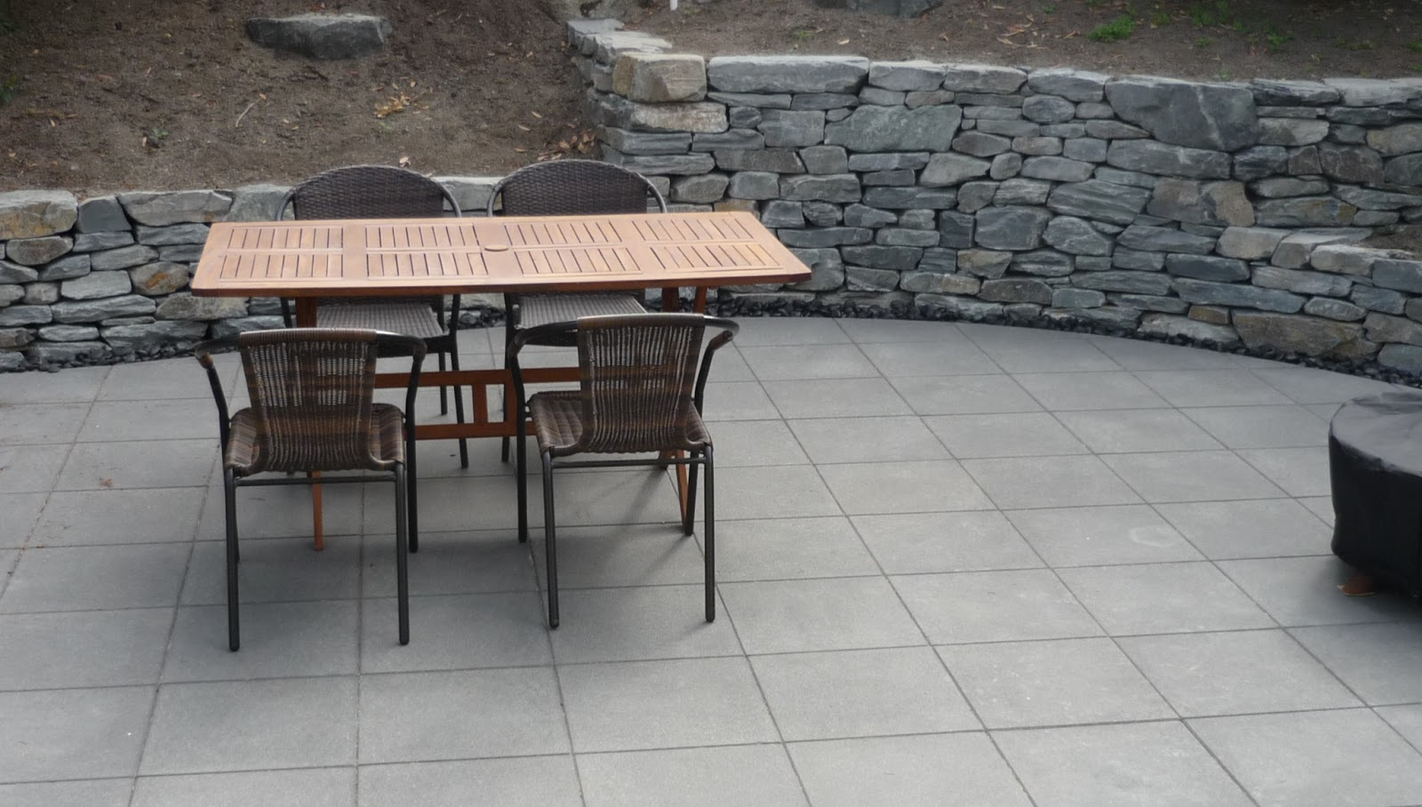 Informal Stacked Stone Walls And Precision Cut Concrete Patio