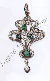 A silver pendant depicting flowering plants with the heads of the flowers represented by heart shaped simulated emeralds. This typical Art Nouveau styling was common in Edwardian jewelry. M id-too-150 ($170-255)