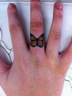 Colorful butterfly tattoo on finger