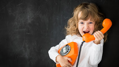 beutiful little girl holding a telephone receiver answering