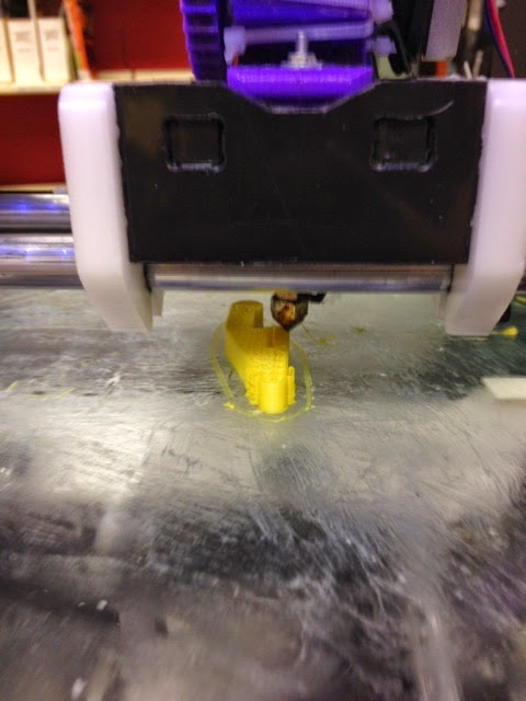 A close up of a 3D printer's nozzle, printing something yellow.