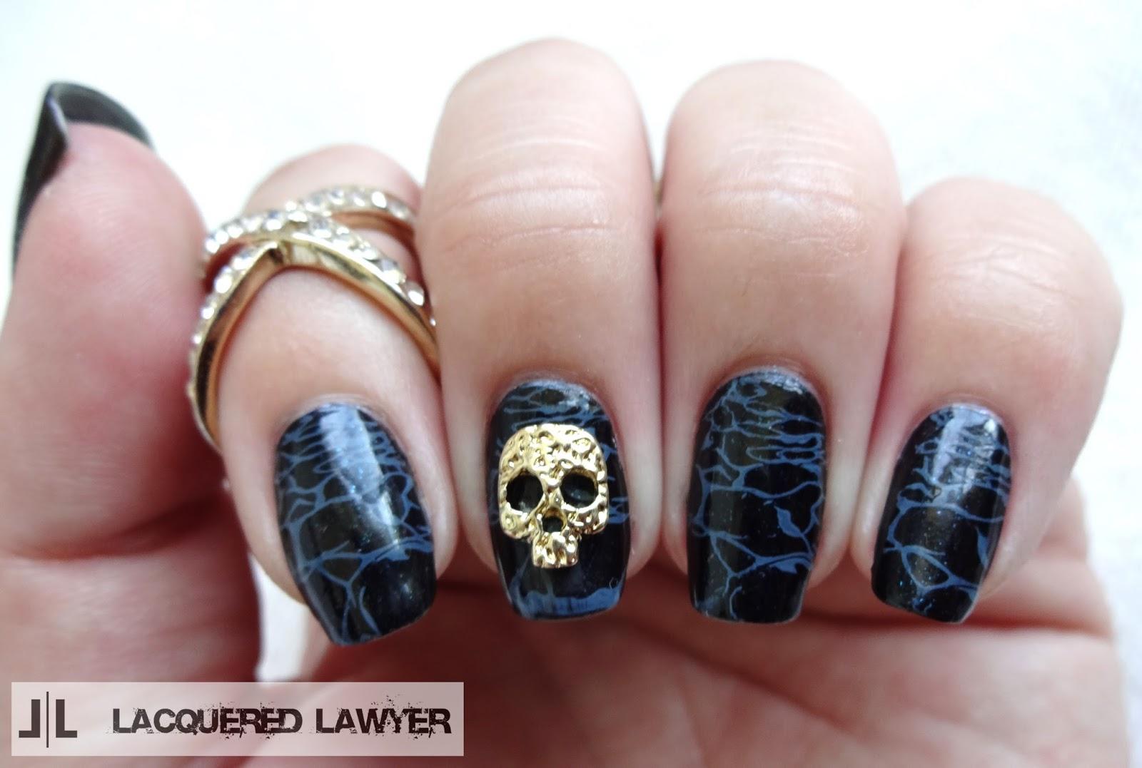 Black sea nail art with gold skull charm