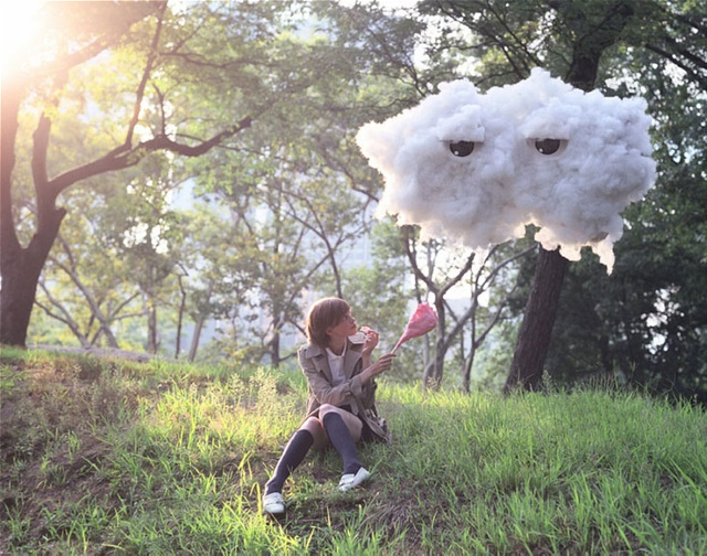 Girl offering candy floss to floating cloud