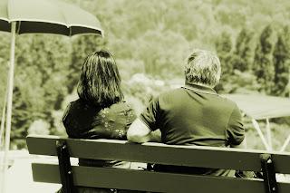 Casal sentado num banco à borda do lago de Annecy