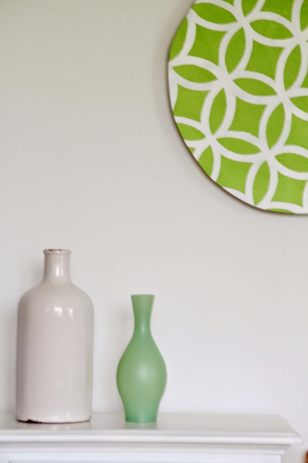 Fertige Wanddeko mit grün weißem grafischem Muster und Vasendeko