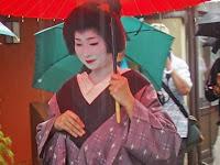 赤い番傘と雨コートを来て挨拶廻りに出掛けた。