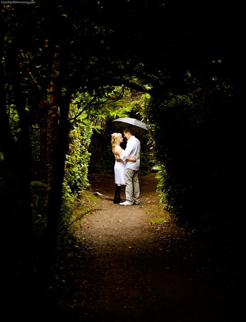 22. A bride and groom walk down a dark path, into a lighted area and share a moment and break from the rainy day Jason van der Valk