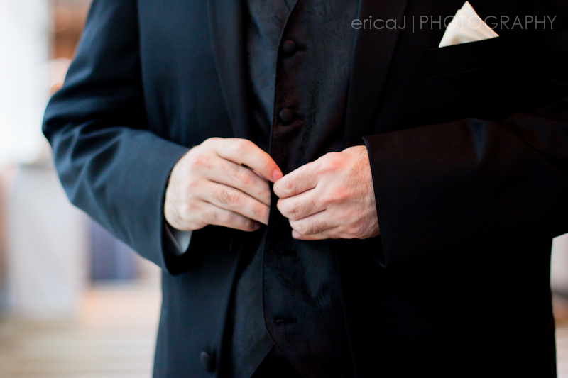 groom buttoning suit jacket
