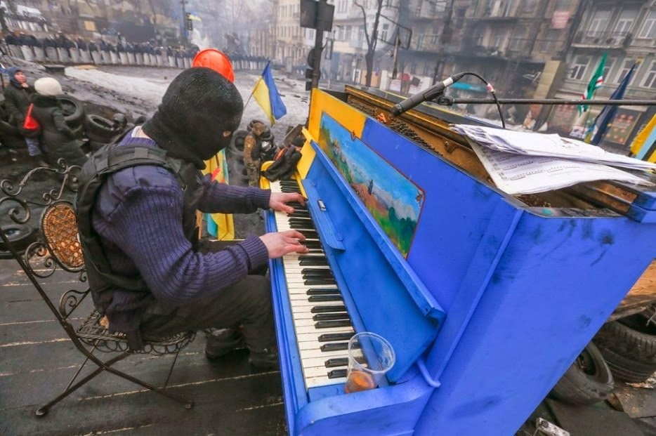 Protester plays piano over the sounds of chaos, with riot police in the backdrop. - The 63 Most Powerful Photos Ever Taken That Perfectly Capture The Human Experience