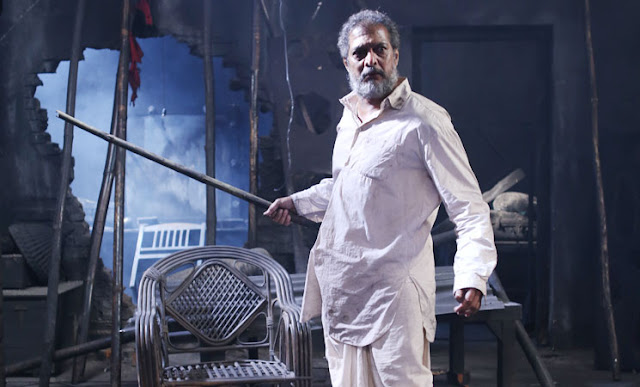 A Still from Mahesh Manjrekar's Natsamrat, Nana Patekar on stage, with a rod