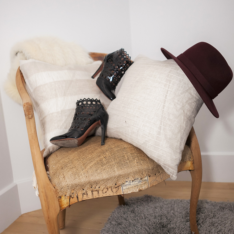 Alaïa eyelet patent leather booties, burgundy Bailey of Hollywood wide brim hat, beige linen pillows, vintage stripped raw meterial wooden chair